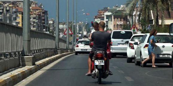 Bir koluyla motosiklet sürdü, diğeriyle çocuk taşıdı